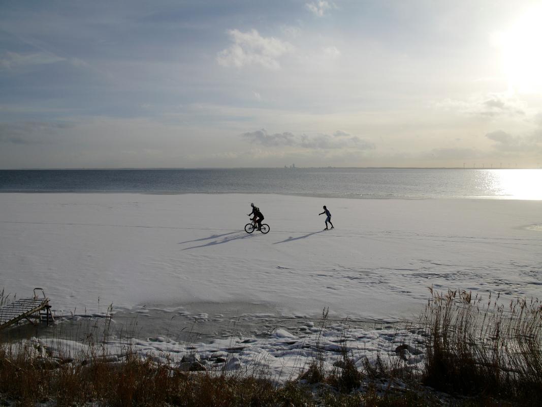 Nederland,  Uitdam , Waterland  31 januari 2010Wintertaferelen in Waterland. Schaatsers en fietser op bevroren gedeelte van het IJsselmeer voor de dijk van Uitdam, met naast hen nog onbevroren water.Foto: Marijke Bresser/ Hollandse Hoogte